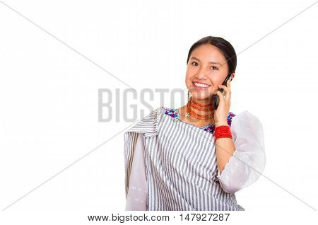 Headshot beautiful young woman wearing traditional andean shawl and red necklace, talking on mobile phone smiling happily, white studio background.