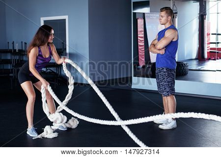 Functional training - young woman doing an exercise with ropes with a trainer