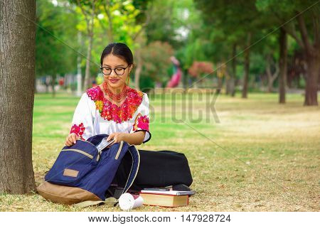 Young woman wearing traditional andean skirt and blouse with matching red necklace, sitting on grass next to tree in park area, relaxing while smiling happily.