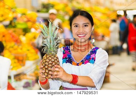 Beautiful young hispanic woman wearing andean traditional blouse posing for camera holding pineapple inside fruit market, colorful healthy food selection in background.
