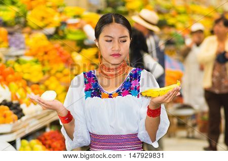 Beautiful young hispanic woman wearing andean traditional blouse posing for camera holding banana and onion inside fruit market, colorful healthy food selection in background.