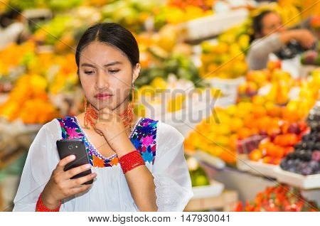 Beautiful young hispanic woman wearing andean traditional blouse using mobile phone inside fruit market, thoughtful facial expression, colorful healthy food selection in background.