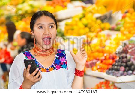 Beautiful young hispanic woman wearing andean traditional blouse holding mobile phone inside fruit market, surprised facial expression, colorful healthy food selection in background.