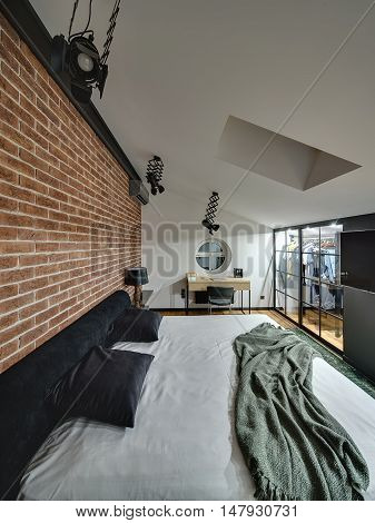 Trendy modern bedroom with cloakroom with glowing lamps, brick wall, bed, table with chair, TV, round window on the wall and window at the top. On the floor there is parquet and green carpet.