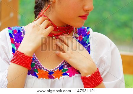 Closeup beautiful hispanic woman wearing traditional andean white blouse with colorful decoration around neck, matching red necklace, bracelet and ear ring.