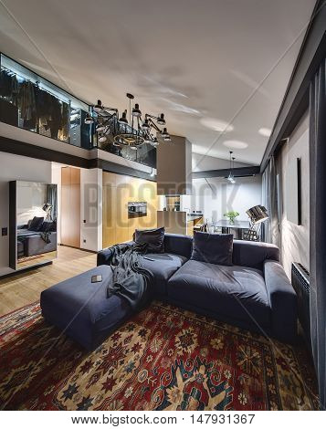 Luminous interior with parquet with red carpet on the floor. There is mirror, wooden cupboard, kitchen island, table with chairs, blue sofa with pillows. Higher there are glowing lamps and cloakroom.