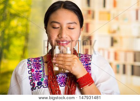 Beautiful hispanic woman wearing white blouse with colorful embroidery, holding and smelling from three small tubes of cream, eyes closed, during makeup routine, garden background.