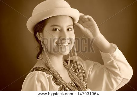Bautiful hispanic model wearing andean traditional clothing with matching hat, smiling happily for camera, studio curtain background, black and white edition.