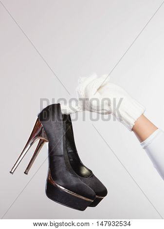 Close up of human hand with black high heels shoes. Female woman fashion.