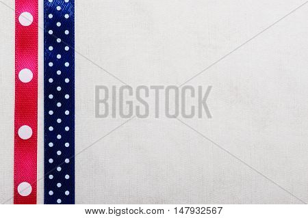 Festive celebration party frame. Polka dot navy blue and pink satin ribbon on white cloth background