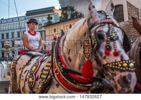 KRAKOW, POLAND - SEP 10, 2016: Old-styled carriage for tourists in the streets of Old Krakow. Krakow is visited by over 8 million tourists a year, number of foreign tourists up to 2 million people.
