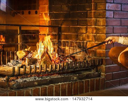 Closeup of human hands with fire iron poker at fireplace. Person heating warming up and relaxing. Winter at home.