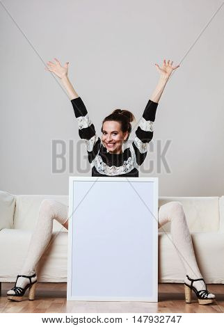 Advertisement concept. Fashionable woman sitting on sofa with blank presentation board. Joyful female model showing banner sign billboard copy space