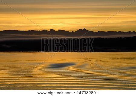 Sunset is reflected in the wake of a cruise ship on the calm waters of the inside passage of Southeast Alaska.