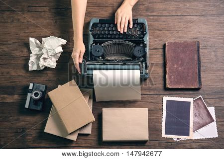 Woman hands working with retro typewriter, camera and photos on wooden background
