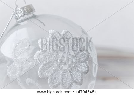 horizontal close up image of a dainty clear christmas ball with white embroidery flower on the ball with room for text.