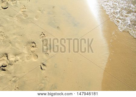 Footprints On A Sandy Beach Being Washed Away By The Sea With The Sun Reflecting In The Waves