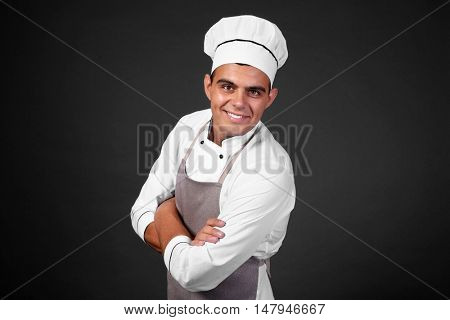 Young handsome chef cook on black background
