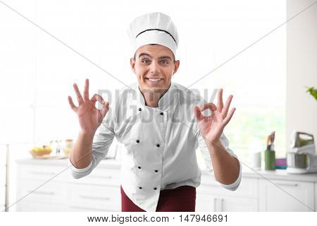 Young handsome chef cook in kitchen