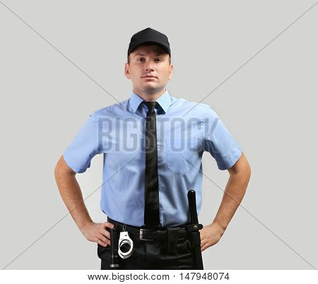 Male security guard on grey background