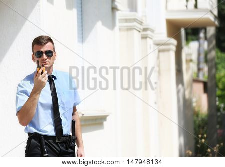 Male security guard with portable radio outdoors