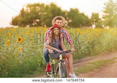 Young couple on bicycle in field