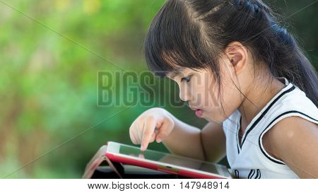 close up on face little Asian girl playing on digital tablet