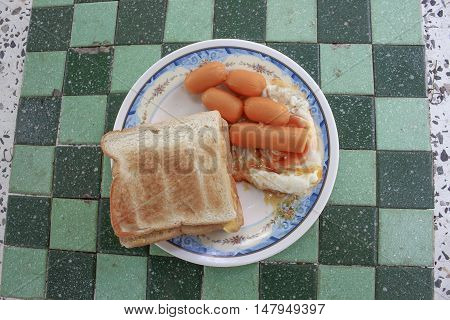 toast breakfast with fried eggs and sausages on stone table close up