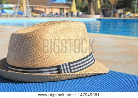 Straw Hat On A Poolside Sunlounger In Early Morning Sunshine