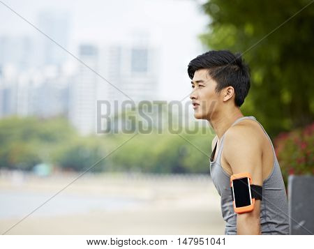 young handsome asian jogger wearing fitness tracker taking a break in a city park