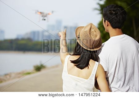 young asian woman pointing to a flying drone operated by her friend or partner