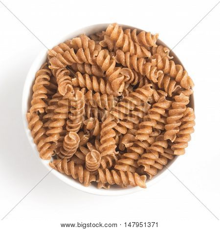 Wholemeal Fusilli into a bowl. Integral Pasta isolated in white background