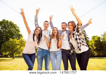 Portrait Of Happy Smiling Friends Gesturing With Raised Hands