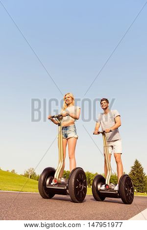 Portrait Of Beautiful Young Woman And Handsome Man Using Segway