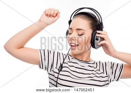 Portrait of pretty girl listening music in headphones and dancing
