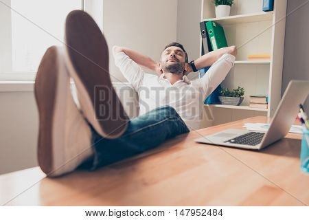 Relaxed Happy Man Sleeping And Holding Legs On Table