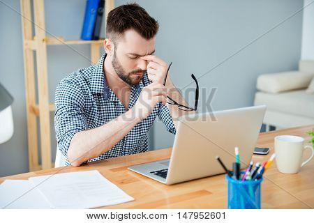 Young Businessman In Office Having Headachev After Working Day