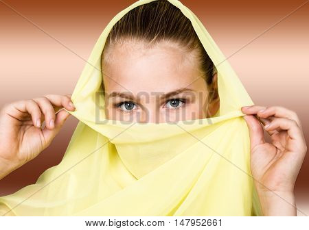 close-up beautiful mysterious eyes eastern woman wearing a yellow hijab.