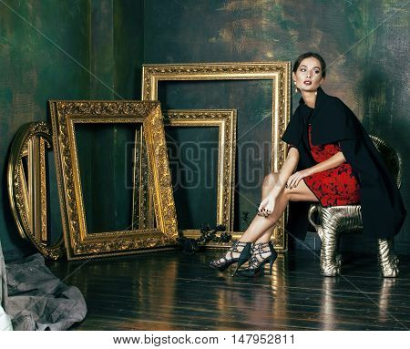 beauty rich brunette woman in luxury interior near empty frames, wearing fashion clothes, lifestyle people concept close up