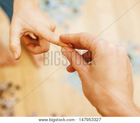little kid playing with puzzles on wooden floor together with parent, lifestyle people concept, loving hands to each other close up