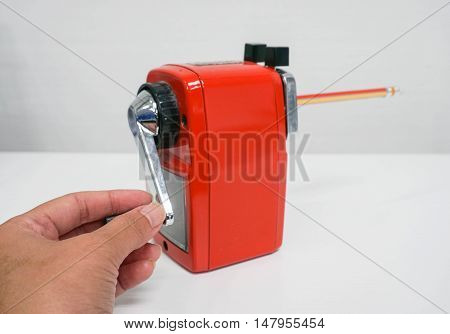 sharpening a pencil using the red sharpener