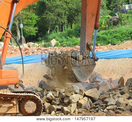 rusty orange bulldozer shovel arm, starting to lift a load of rocks, forest trees and greenish tarp in the background, Songkhla, Thailand
