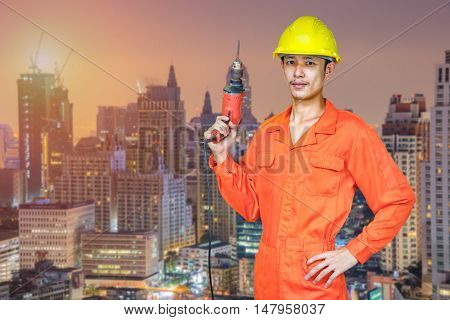 Asian young man worker of construction city project on blurred bangkok building background. heavy industry concept