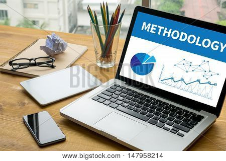 METHODOLOGY Laptop on table. Warm tone businessman work hard and use computer