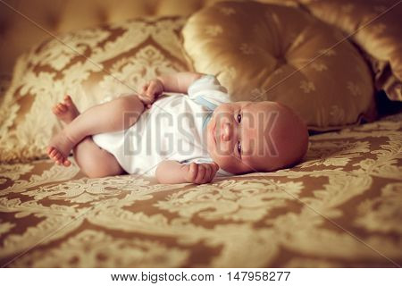 newborn healthy baby 2 weeks old is lying in a posh bedroom on the parent's bed and smiles. A small child in the comfort of your room