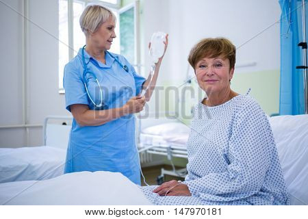 Portrait of smiling patient sitting on bed and nurse checking glucose bottle in background at hospital