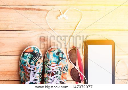 colorful Canvas shoe white Earphone with sunglasses and Tablet on wooden background with warm tone. accessories for travelling. I love to relax