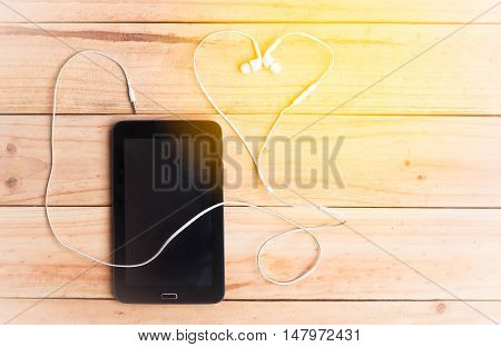 The Heart Shape Of White Earphone And Tablet On Wooden Background With Warm Tone.