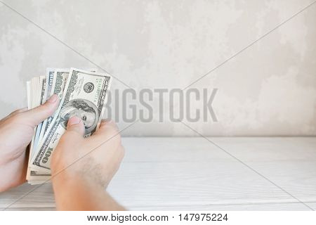 Hands counting american money, free space. Close up of batch of one hundred dollar bills, white wall background. Income count, salary, earning concept