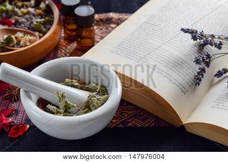 natural apothecary with essential oils, herbs and book